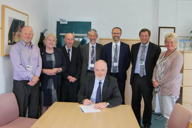 Principal David Walrond signing the mental health charter with senior  management colleagues