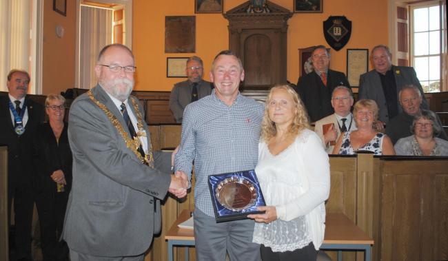 Mayor John Martin presents Alan Goldsworthy and Sue Mallinder with their award in front of councillors