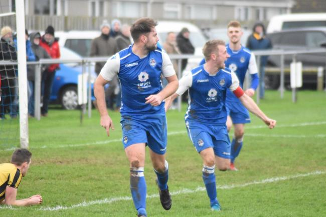 Olly Brokenshire wheels away in celebration after scoring the opening goal of Helston Athletic's 3-0 win over Falmouth Town