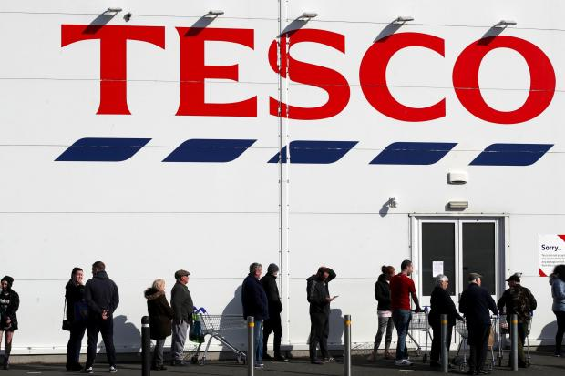 Falmouth Packet: People queue outside a Tesco Extra store in Madeley, Shropshire