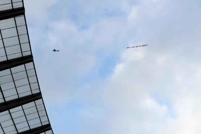 A plane flies over the Etihad Stadium with a banner reading 'White Lives Matter Burnley'