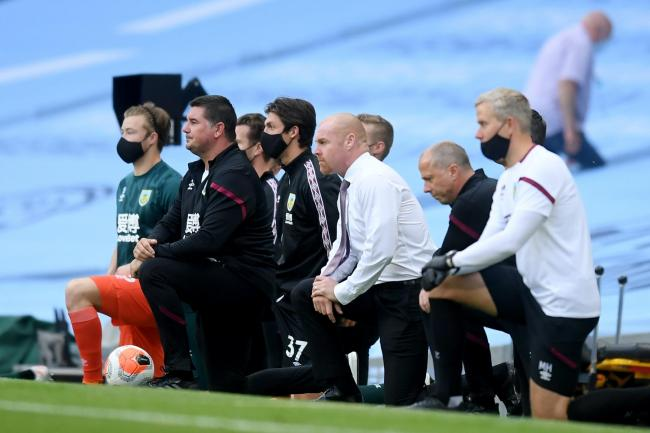 Burnley manager Sean Dyche and his staff take the knee