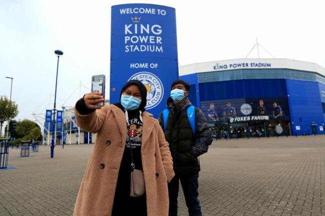 Two people taking a selfie outside the King Power Stadium in Leicester