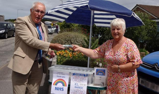Dr Ken Whittle, president of the Helston Hospital League of Friends, receives £1,250 raised from the sale of the masks by Paula Julian
