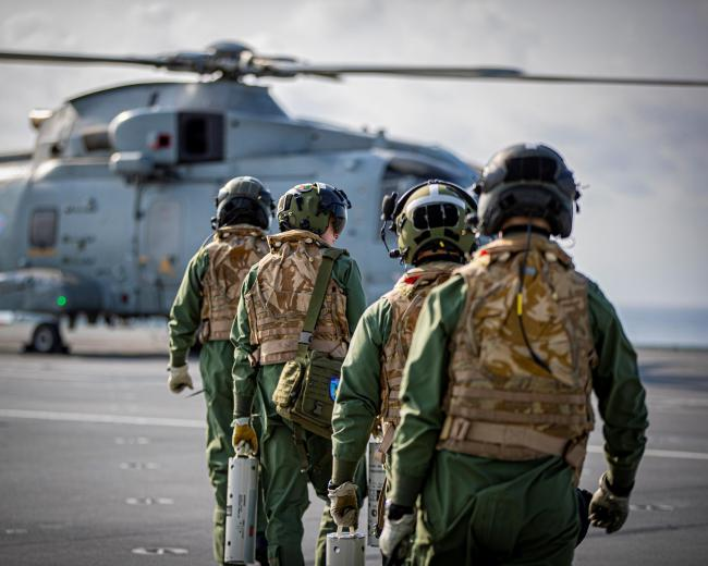Aircrew walk towards their Merlin Mk2 helicopter on HMS Queen Elizabeth