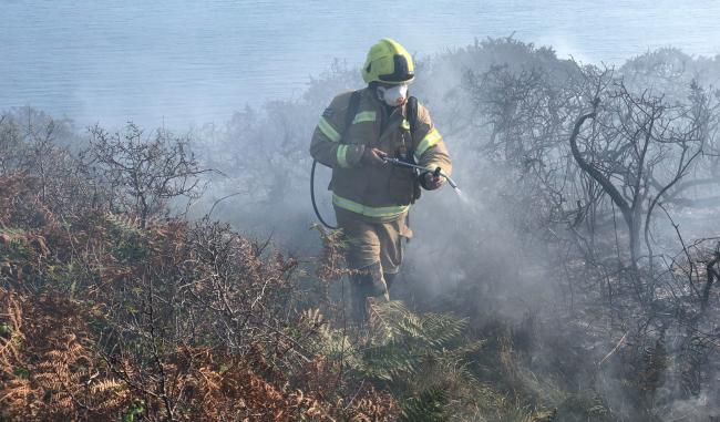 A fire fighter sprays down the burnt gorse. Photo: Penzance Fire Station