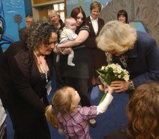 Three-year-old Abby Brown presents Camilla, the Duchess of Cornwall with a posy while WILD project manager Jo Davies watches on
