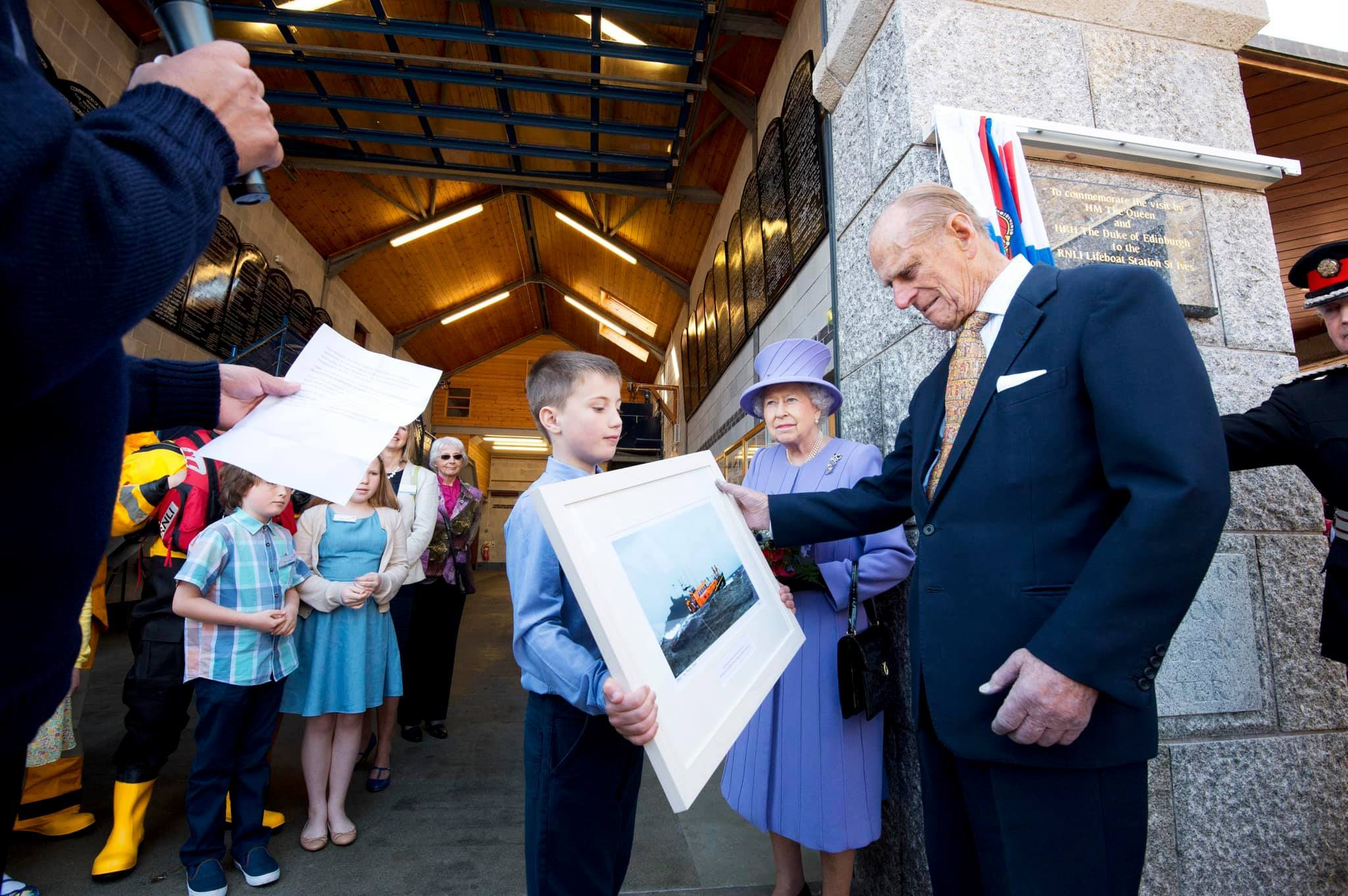 The Queen and Prince Philip are presented with a print on a visit to St Ives Lifeboat Station. Picture: St Ives RNLI