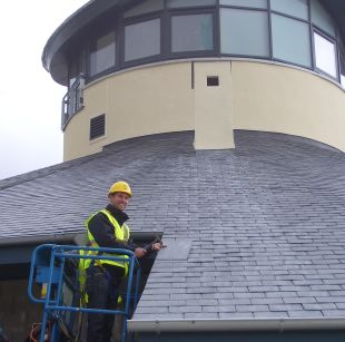 Pirate FM Presenter Neil Caddy placing the last tile on the roof of Little Harbour
