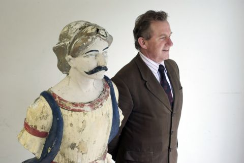 Auctioneer David Lay with the fiberglass copy of the figurehead from HMS Foudroyant
