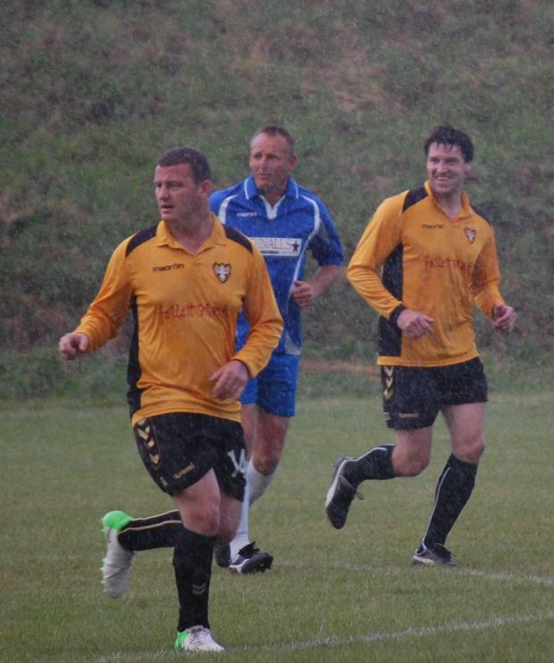 Sid Taylor, centre in action for Helston during the match against Falmouth