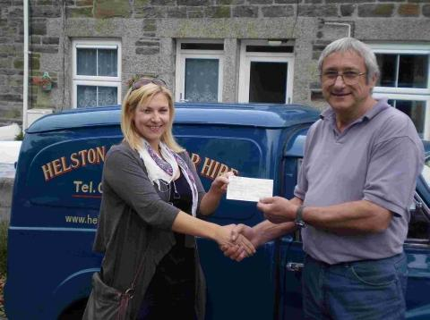 ick Timpson from Helston Rotary Club presents a cheque for £250 to Siobhan Harvey for the Beating Bowel Cancer Borneo Trek.