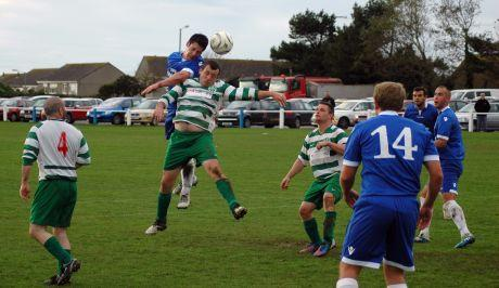 Players challenge for the ball during Helston's 7-0 drubbing of Mousehole FC on Saturday