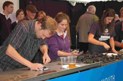 Frantic shucking action as the first competitors take to the stage for the timed oyster opening event