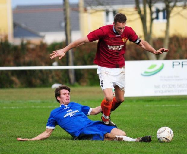 Helston midfielder Tom Russel makes a great tackle during the Blues' cup win over Godolphin - Photo: Phil Ruberry