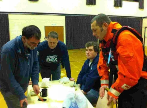 ShelterBox Response Team members (L-R) Joe Cannon, James Edgerley and Ray Filbey discuss tactics with Stuart Williams, watch commander for the Cornwall Fire and Rescue Service.