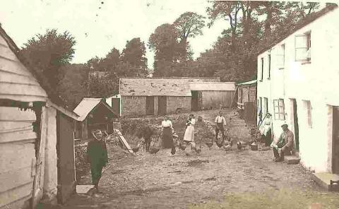 Postcard of a farmyard believed to be in the Helston area, showing seven people including possibly the local minister. Donated by Mrs J Larsen.