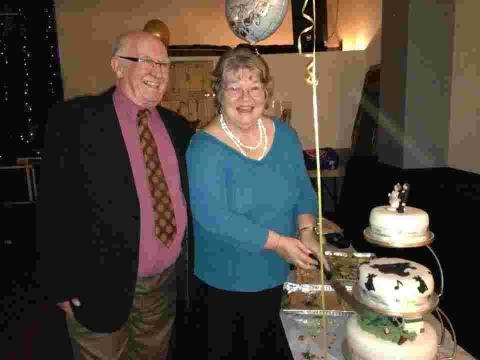 Gerald and Angela Symonds cut the cake at their surprise party