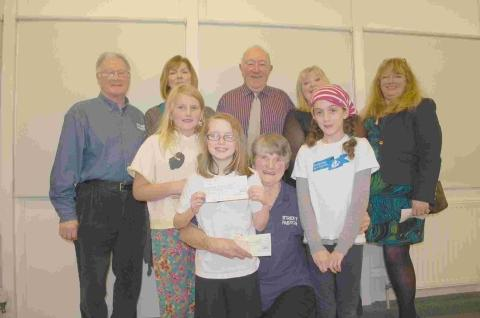 Harmony choir hands funds to good causes