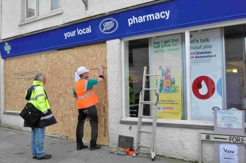 Workmen board up the window of Boots Pharmacy in Porthleven on Saturday