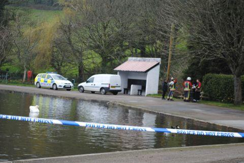 Police and firefighters at Coronation Lake on Saturday morning, after a fire took place in the woodland behind