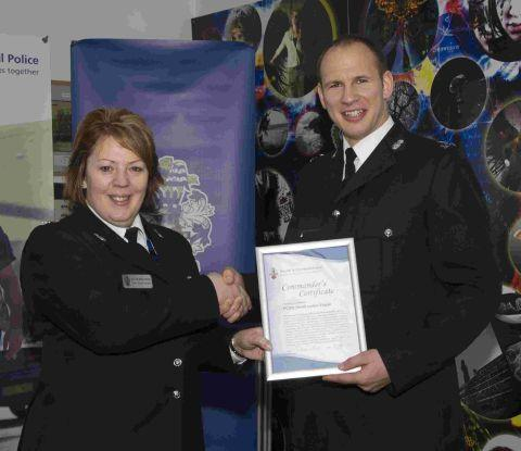 PCSO Lewis Vague accepts his commander's certificate from Supt Fielding