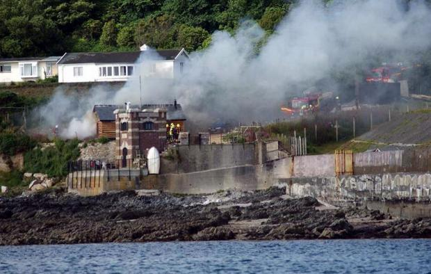 Falmouth Packet: Fire crews tackle the shed fire on Pendennis Point. Credit: Orca Sea Safaris