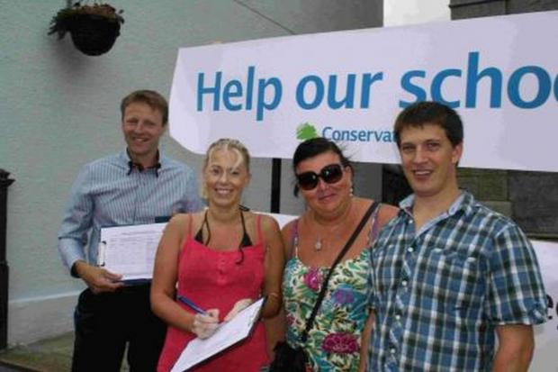 The Conservatives, gathering signatures in front of a large Conservative party banner, say the petition is not about 'party politics'