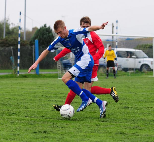 Falmouth Packet: Helston striker Mark Goldsworthy pictured battling for the ball as they looked to get back on level terms