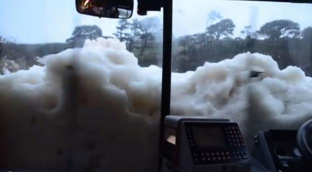 Deep foam up to the bus windows at Poldhu was not going to stop this driver: Spectacular VIDEO