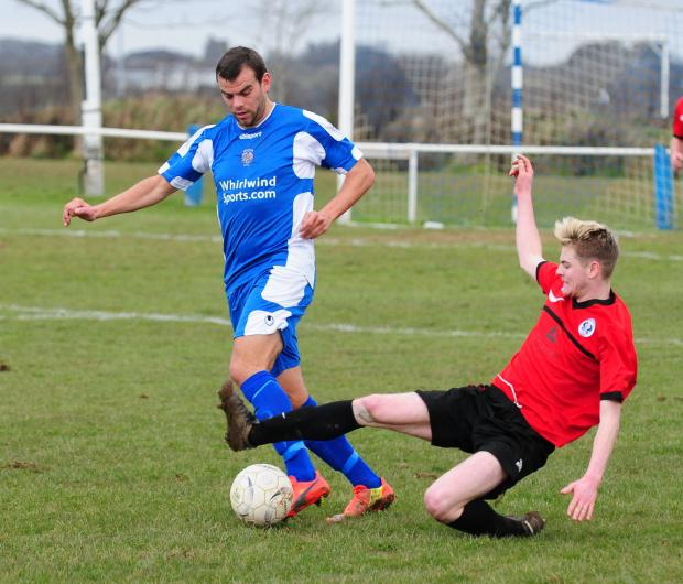 Helston's Dan Stidwell is challenged for the ball