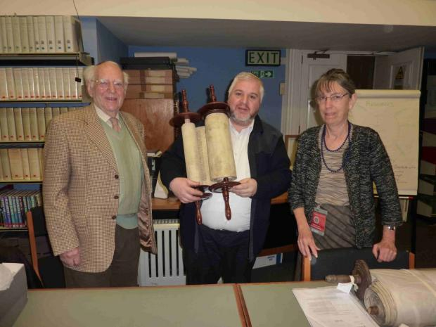 Falmouth Packet: Torah ccribe Bernard Bennaroch holding the scroll with Leslie Lipert of Kehillat Kernow and Angela Broome, archivist librarian at The Royal