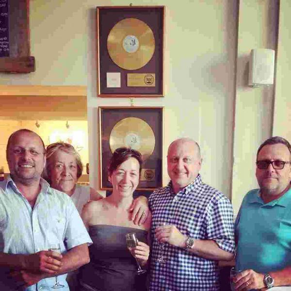 Amélies owner Sam Sheffield-Dunstan with her brothers and mum Chris hanging the gold discs