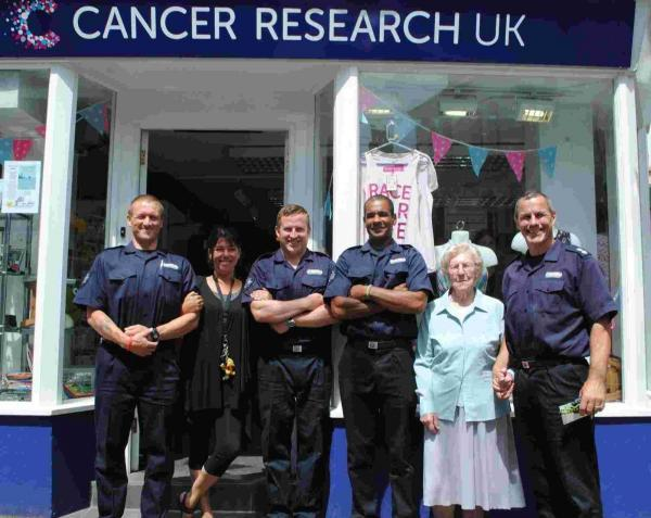 Falmouth firefighters hand over Trident Swim funds to Cancer Research