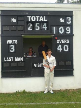 Luke Tripconey standing proudly by the scoreboard showing his century