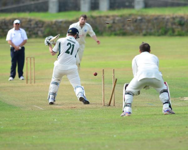 Beacon batsman Daniel Thurgood sees his middle stump uprooted by Helston's Tom Retallack