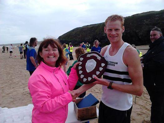 Ben Price receives the winner's shield after coming first in the St Ives 10k