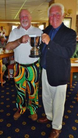 Jim McClung and his impressive trousers receiving the trophy from Mullion Golf Club president Jimmy Stewart