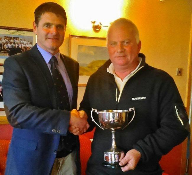 Dale Wilson receives the Cyril Lane Cup from Mullion club captain Nigel Thwaites