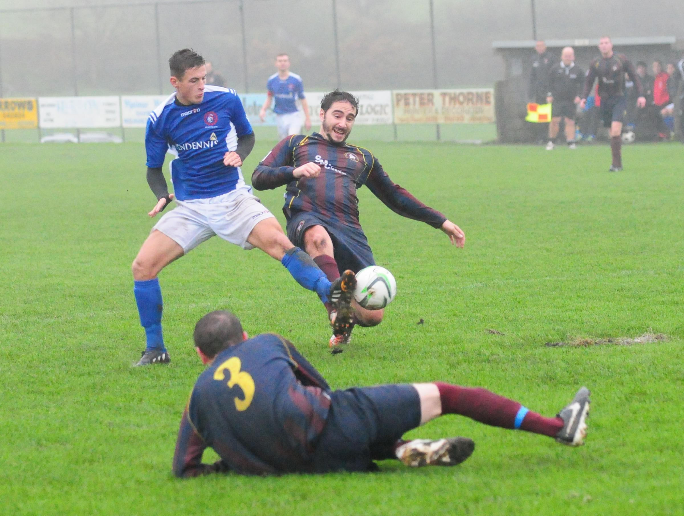 Penryn striker Dave Broglino is thwarted by Wendron defender Matt Rose during Saturday's windswept derby at Underlane in Division 1 West of the South-Western Peninsula League.