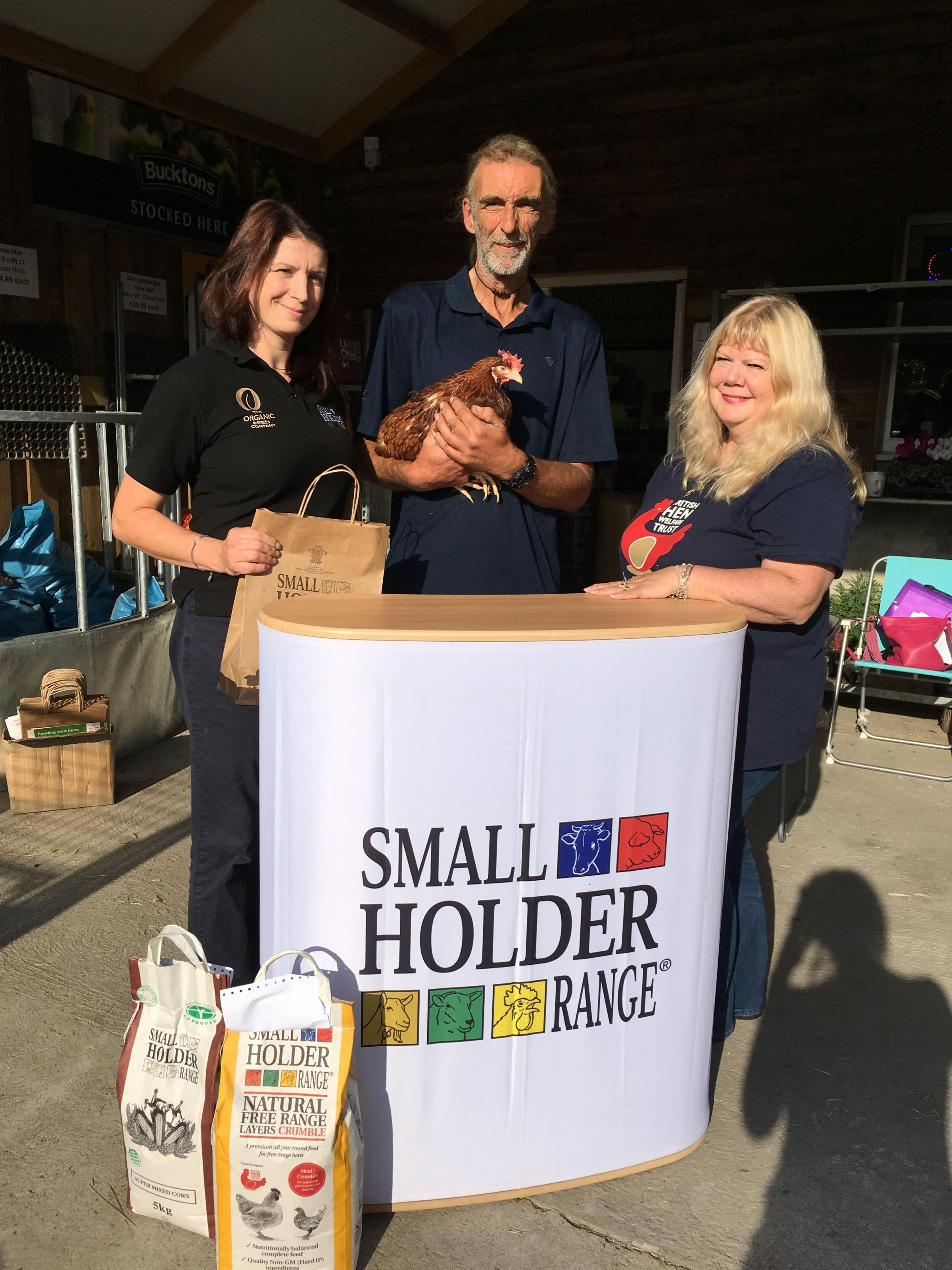 : David Godwyn, who re-homed the 1,000th hen from the BHWT's Redruth team on Sunday, with Isabel Greenaway from Allen & Page who are giving him some hen feed as a gift, and volunteer Babs Sherriff.