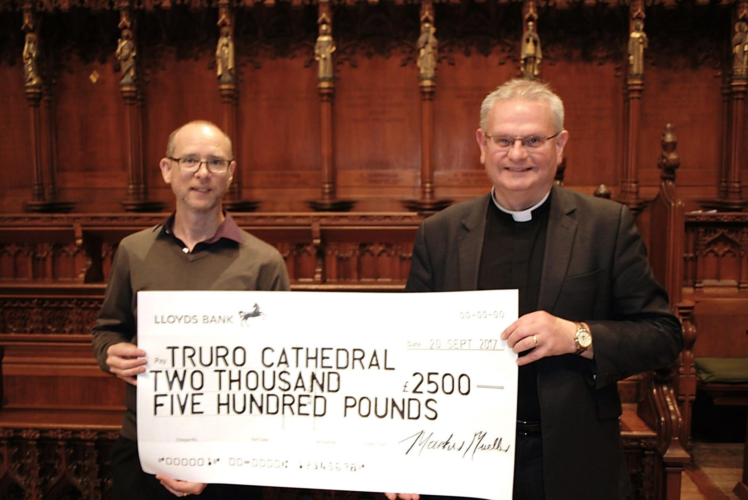 Philip Montgomery-Smith, Truro Symphony Orchestra leader, presents the Very Rev'd Roger Bush, Dean of Truro with a cheque for £2,500 which was raised from a fundraising concert.