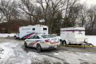 Police vehicles are parked outside a property in Toronto where officers recovered the remains of at least six people from planters (Rob Gilles/AP)