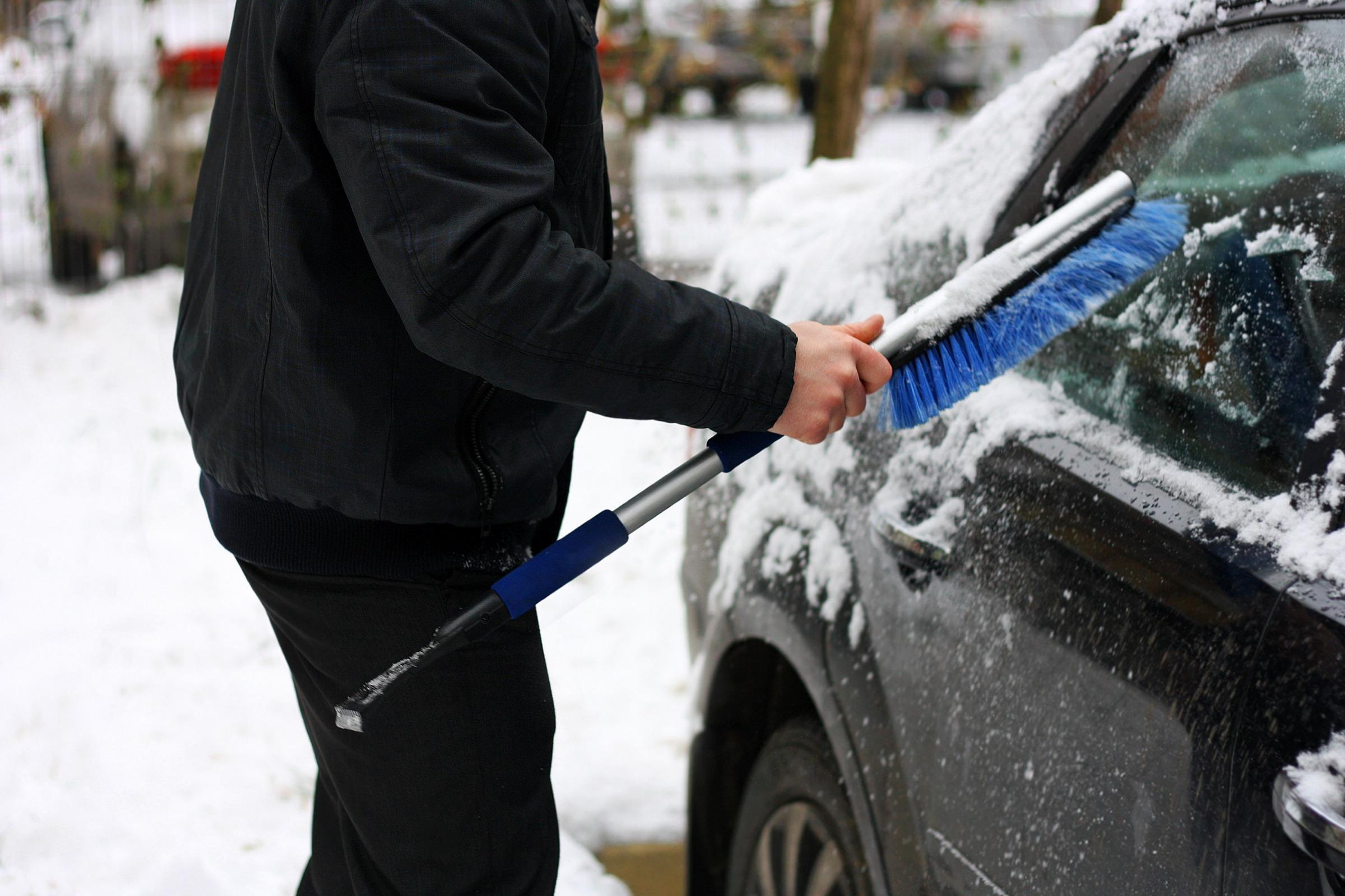 Snowy winter. The snow machine. A man cleans snow from the car with the help of special brushes..
