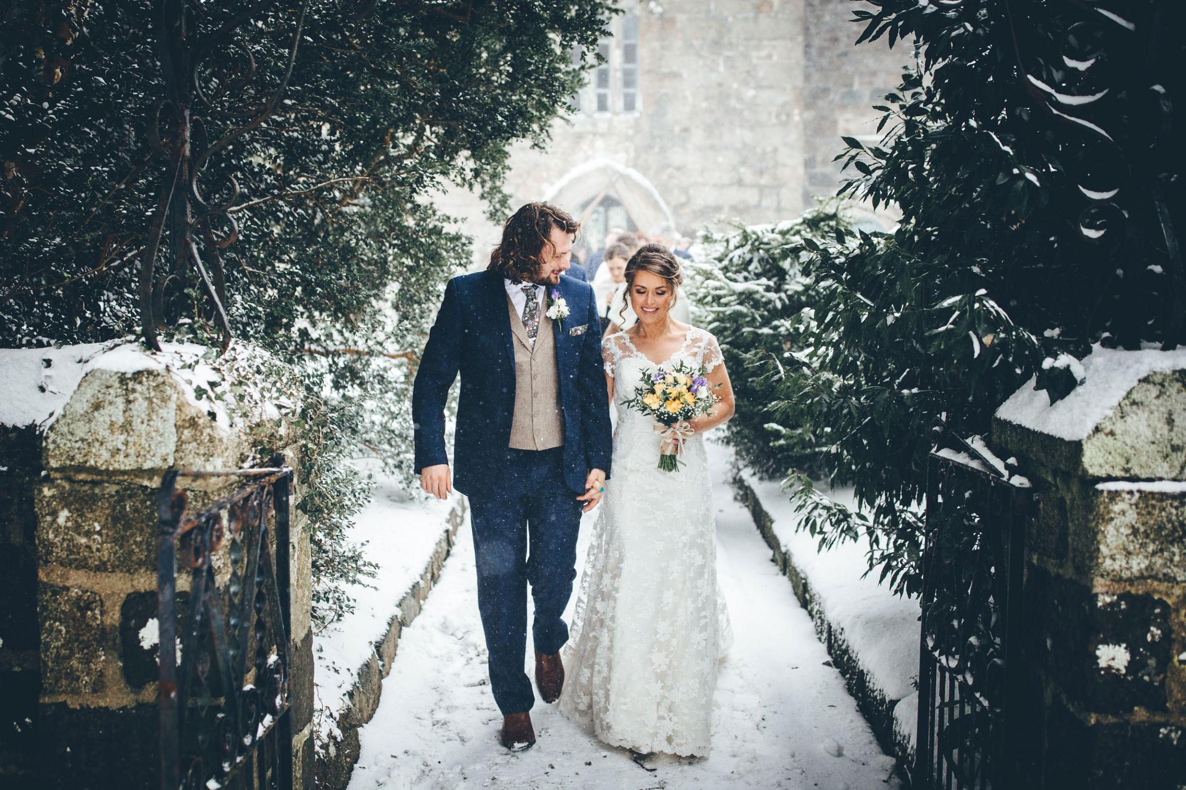 Sam and Katie leave St Martin Church in the snow. Photos: Toby Lowe Photography