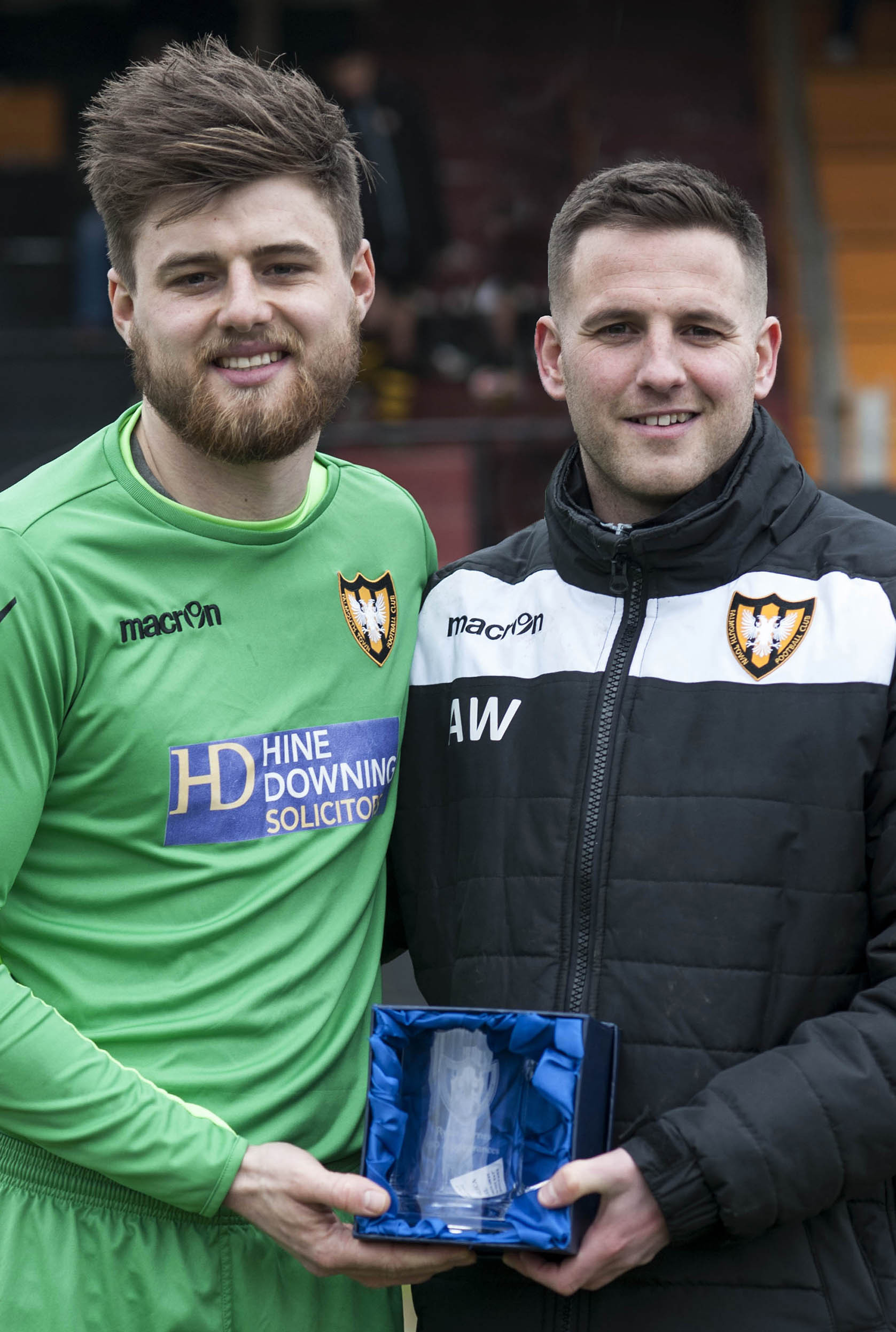 Falmouth Town manager Andrew Westgarth (right) presents an engraved tankard to goal keeper Ryan Barnes before the start of his 100th appearance for the club on Saturday. Picture by Colin Higgs