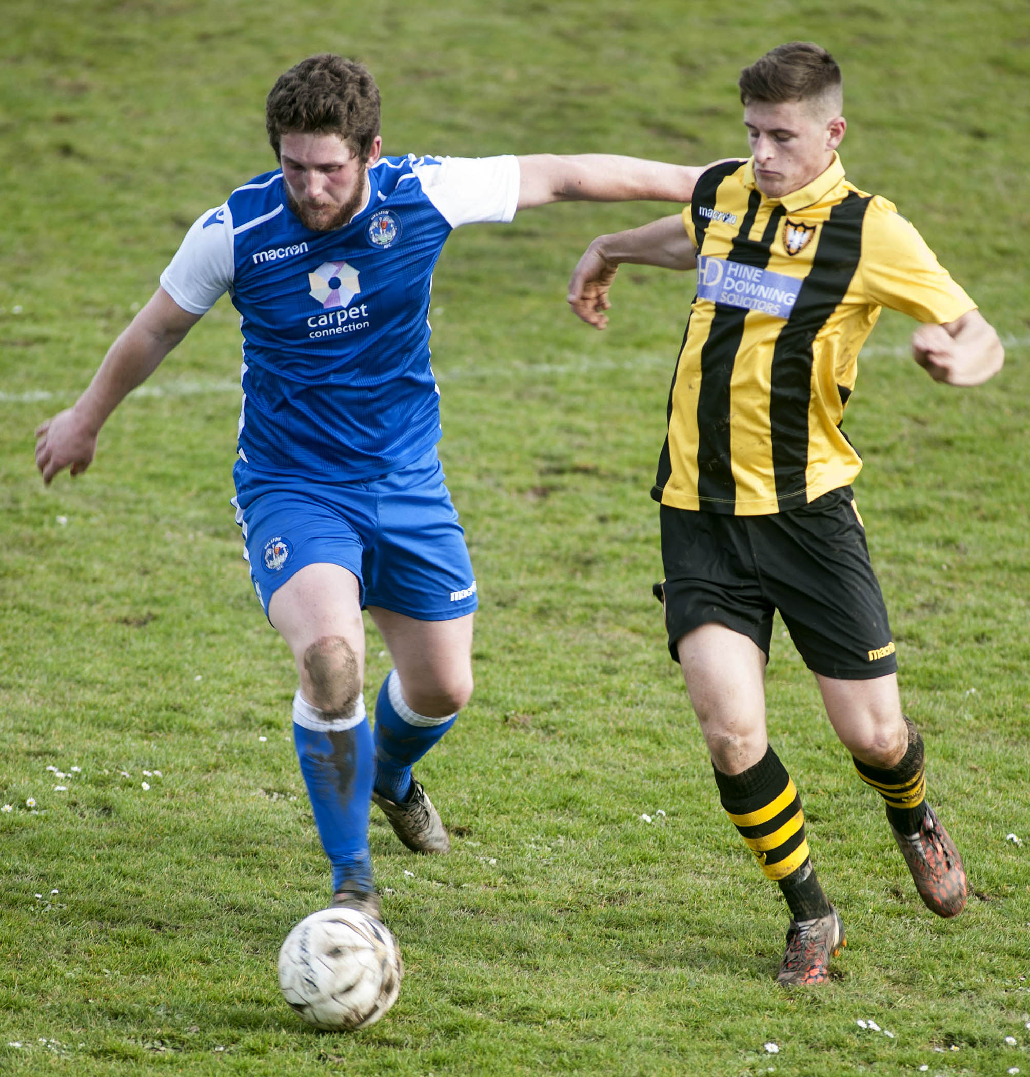 Helston Athletic midfielder Charlie Young (left) goes head-to-head with Falmouth Town's David Broglino (right) during Falmouth's 3-1 win at Bickland Park in March