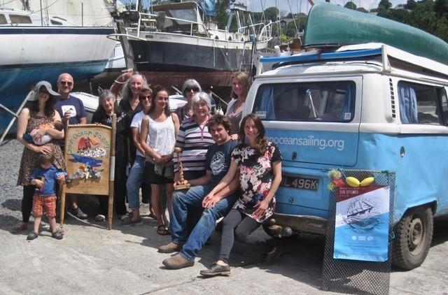 Clean Ocean Sailing founders Steve Green and Monika (seated), plus volunteers, receive the award from members of Lizard Peninsula Friends of the Earth