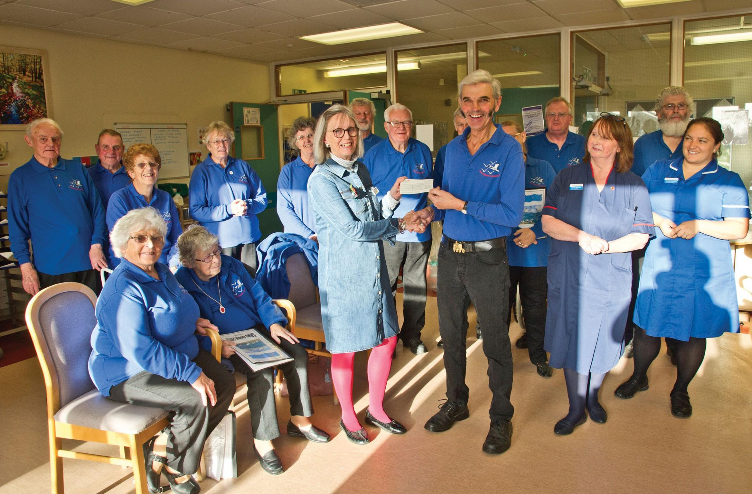 Cecil and Deborah Bennetts, on behalf of the Singing Seagulls, present a cheque for £2,500 to Jo Coward of the League of Friends of Helston Community Hospital. Photo: John Martin