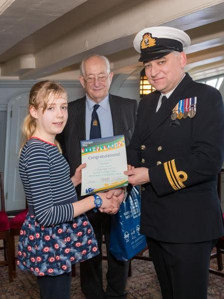 Eva Reid receives her winner's certificate from Lt Cdr Brian Smith, Commanding Officer of HMS Victory, watched by Bill White, vice-chairman of The 1805 Club.
